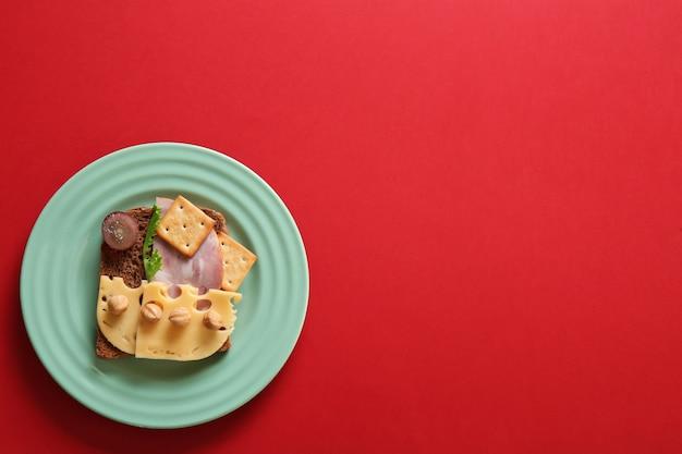 Bord met creatieve sandwich op rode achtergrond