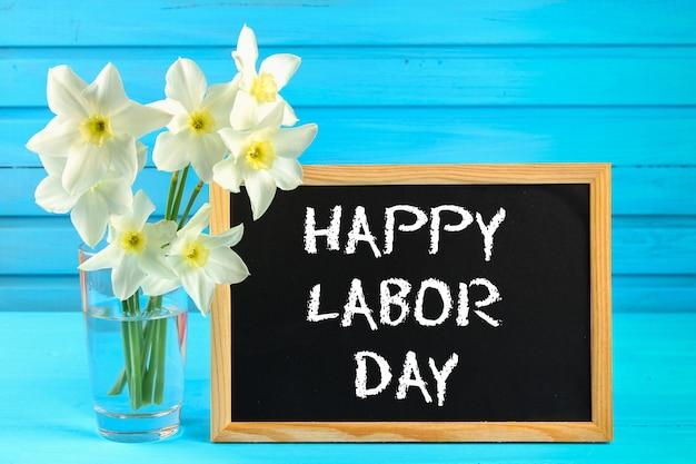 Bord met de tekst: happy labor day, 1 mei. witte bloemen van narcissen op een blauwe houten tafel.