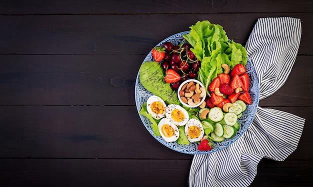 Bord met een paleo dieetvoeding. gekookte eieren, avocado, komkommer, noten, kersen en aardbeien. paleo ontbijt. bovenaanzicht