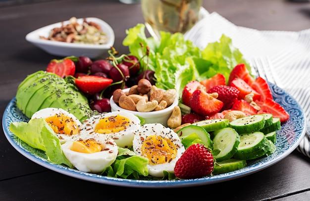Bord met een paleo dieetvoeding, gekookte eieren, avocado, komkommer, noten, kersen en aardbeien, paleo-ontbijt.