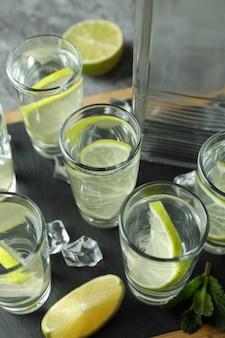 Bord met fles en schoten van drank met kalk op grijze muur