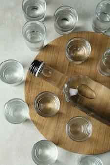 Bord met fles en schoten van wodka op wit gestructureerd oppervlak