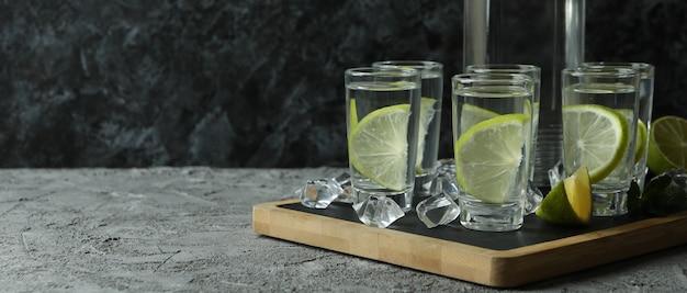 Bord met fles en shots drank met limoen op grijze tafel
