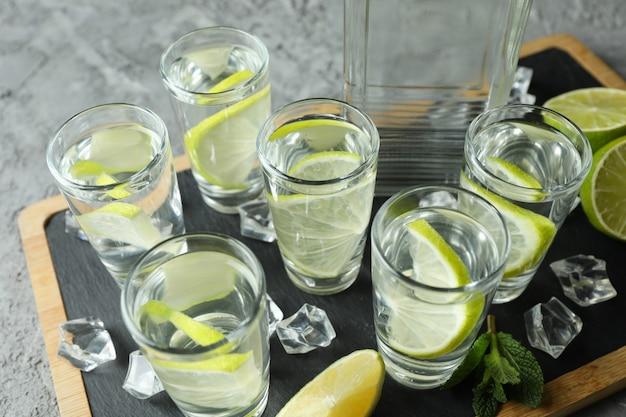 Bord met fles en shots wodka met limoen op grijze ondergrond