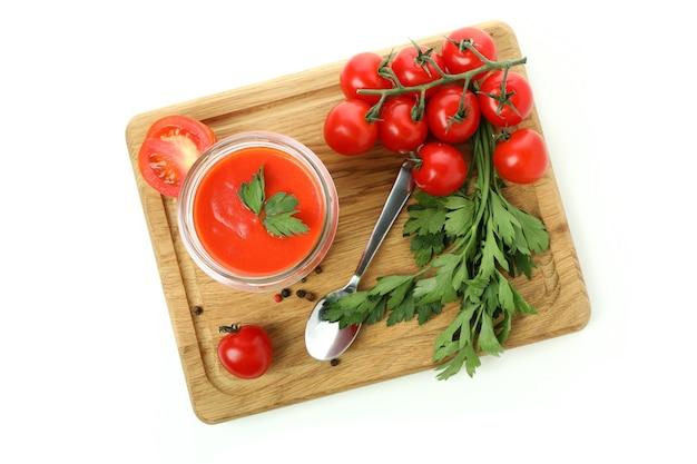 Bord met gazpacho en ingrediënten geïsoleerd op een witte achtergrond