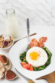 Bord met gebakken ei met spinazie; spek en tomaten op witte achtergrond