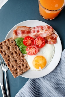 Bord met gebakken eieren, spek, tomaten, jus d'orange en toast.