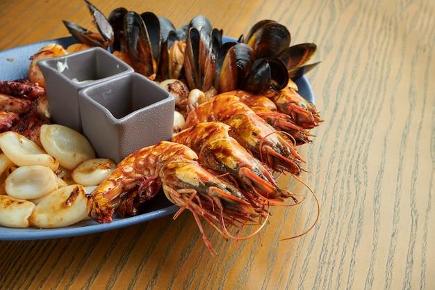 Bord met gefrituurde zeevruchten - mosselen, octopussen, sint-jakobsschelpen, inktvis en garnalen. antipasto. sluit het zicht. houten oppervlak