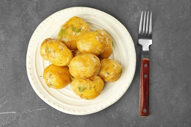 Bord met gekookte aardappelen op grijze tafel