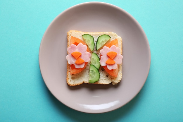 Bord met grappige sandwich op gekleurde achtergrond