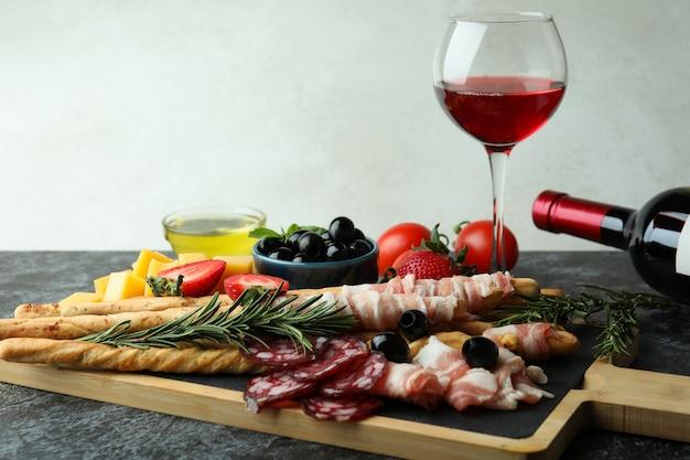Bord met grissini en snacks, en wijn op zwarte smokey-tafel