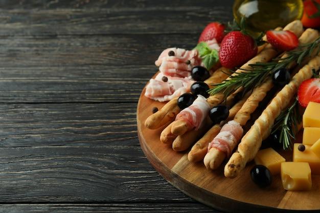 Bord met grissini en snacks op houten oppervlak