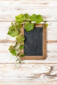 Bord met groene wijnbladeren decoratie op lichte houten achtergrond