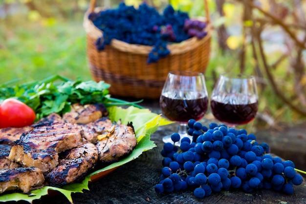 Bord met grote stukken varkensvlees geroosterd op de grill, glazen wijn en druiven in een mand op een houten tafel. picknick in de natuur in de herfst.