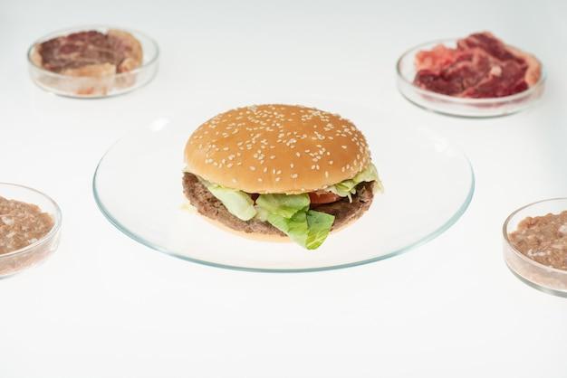 Bord met hamburger op tafel tussen vier petrischalen met verschillende monsters van rauw plantaardig vlees in het laboratorium voor voedselkwaliteitscontrole