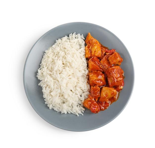 Bord met heerlijke kip tikka masala en rijst op wit wordt geïsoleerd