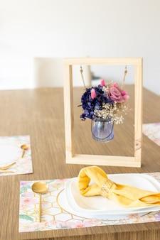 Bord met keukengerei, op tafel versierd met een klein bloemstuk