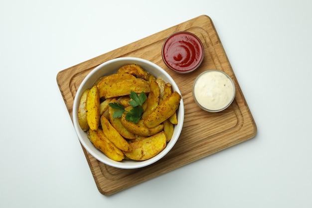 Bord met kom aardappelpartjes en sauzen op wit