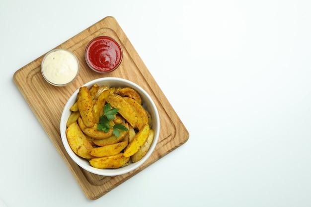 Bord met kom aardappelpartjes en sauzen op witte achtergrond
