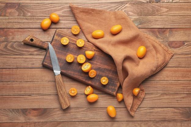 Bord met lekker kumquat fruit en mes op houten tafel
