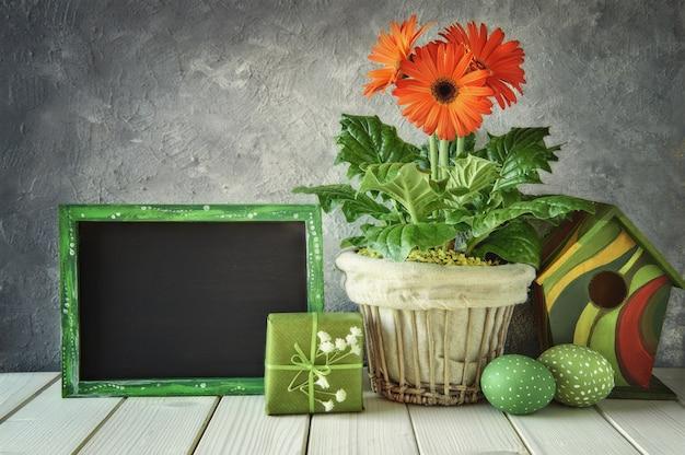 Bord met lentedecoraties: oranje gerbera's, lelietje-van-dalen, vogelhuisje en paaseieren,