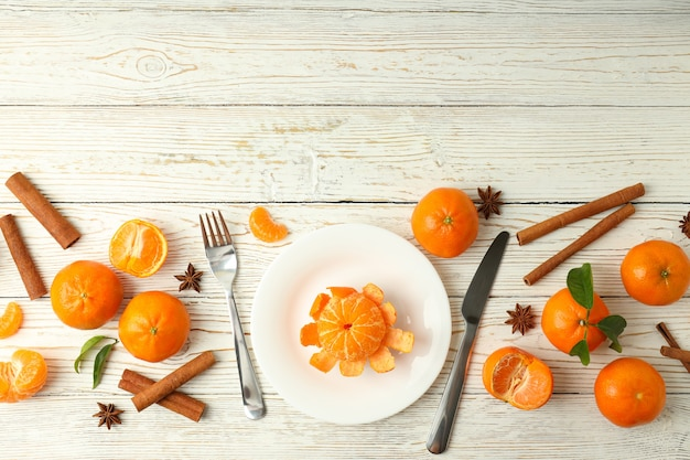 Bord met mandarijn, kaneel, bestek en mandarijnen op witte houten achtergrond