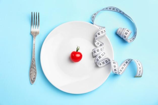 Bord met meetlint, tomaat en vork op blauw