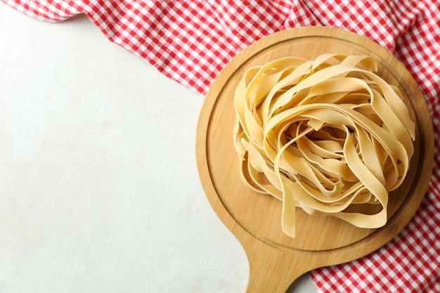 Bord met ongekookte deegwaren en keukenhanddoek op geweven wit