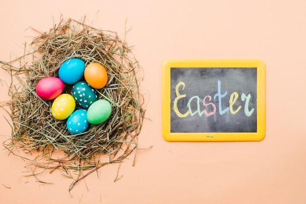 Bord met pasen-titel dichtbij reeks heldere gekleurde eieren in nest