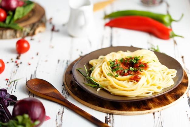 Bord met pasta. kers, chili, tomaat, basilicum, kruiden, dragon, ui