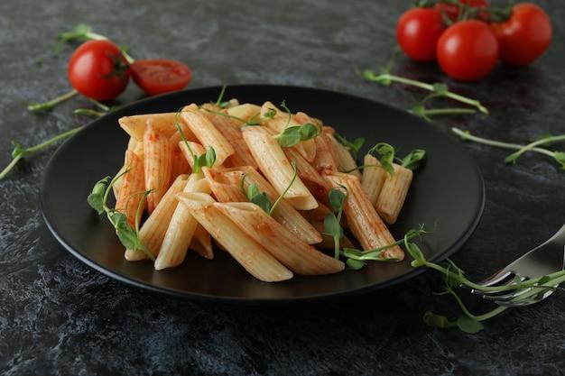 Bord met pasta met tomatensaus, ingrediënten en vork op zwarte smokey-tafel