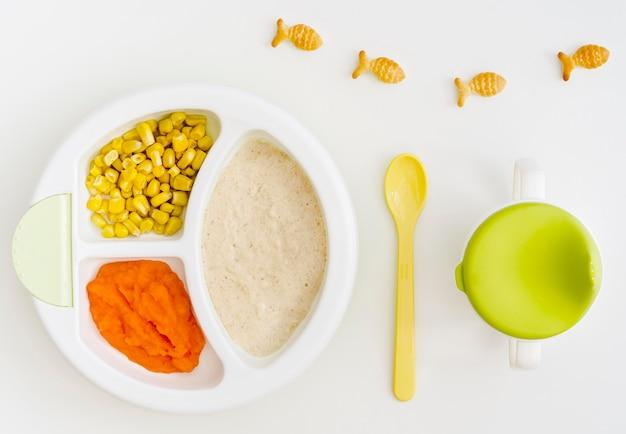 Bord met puree en maïs voor de baby
