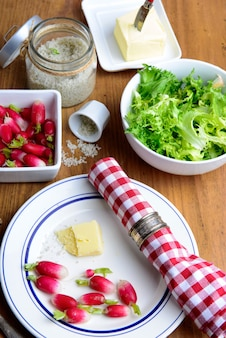 Bord met radijs, boter en salade op een rustieke tafel