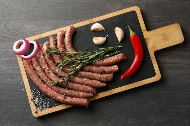 Bord met rauwe worstjes, kruiden en specerijen op donkere tafel
