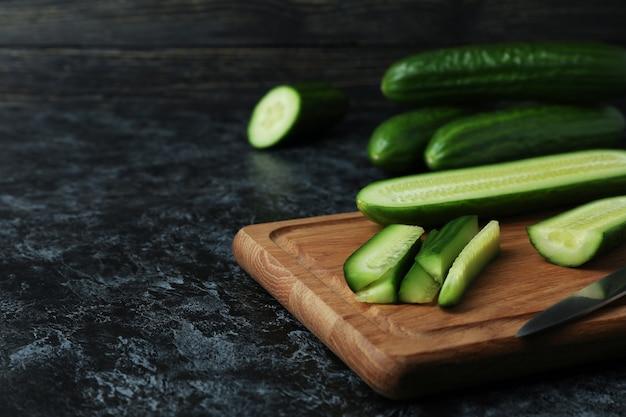 Bord met rijpe komkommer en mes op zwarte smokey tafel