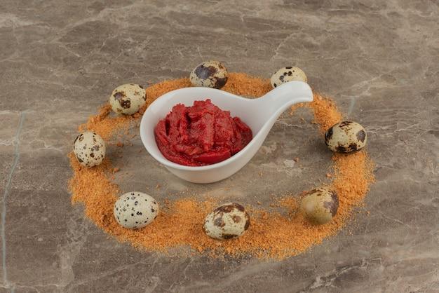 Bord met saus met kwarteleitjes en kruimels.