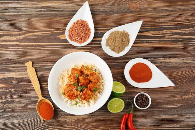Bord met smakelijke kip tikka masala, rijst en kruiden op houten tafel