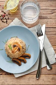 Bord met smakelijke risotto op houten tafel
