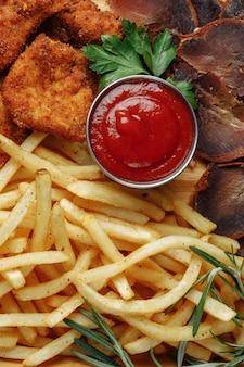 Bord met snacks. gepaneerde kipnuggets, gebakken aardappelen en jamon.