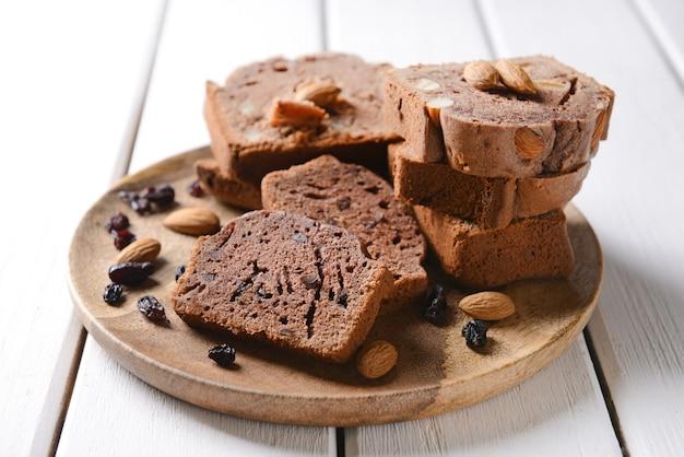 Bord met stukjes smakelijke chocoladetaart op witte tafel