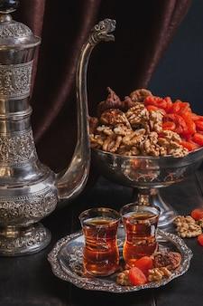 Bord met thee in armuda glazen, vintage kan, een vaas met gedroogd fruit