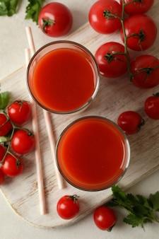 Bord met tomatensap en tomaten op witte gestructureerde achtergrond