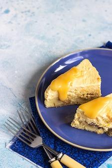 Bord met twee stukjes pompoen cheesecake en met karamel topping op een blauwe keramische plaat