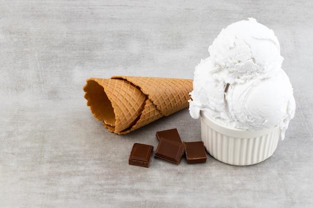 Bord met vanille-ijslepels en chocoladestukjes en wafelkegels.