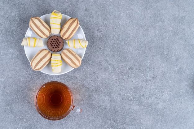 Bord met verschillende koekjes en een glas thee op marmeren oppervlak
