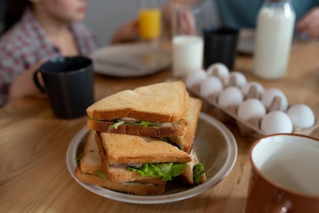 Bord met verschillende smakelijke zelfgemaakte sandwiches met kip en sla op houten tafel tussen mokken. melk en eieren