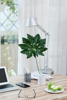 Bord met verse groene appels, laptop en bril op bureau in thuiskantoor van ondernemer