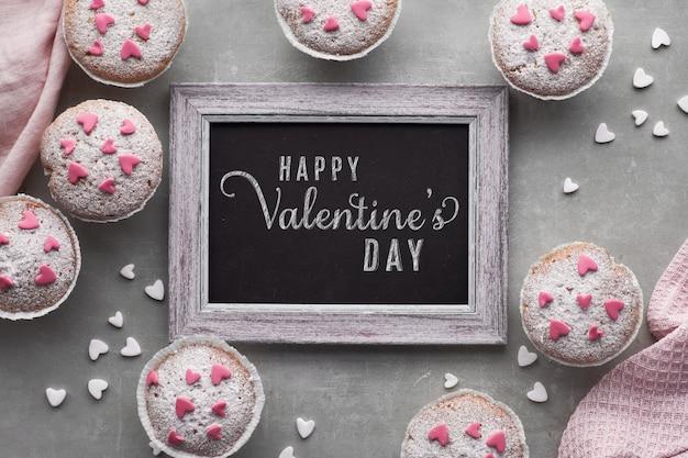 Bord omlijst met suiker bestrooide muffins met roze en witte fondant glazuur harten, tekst