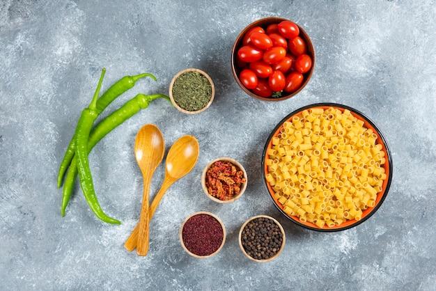 Bord pasta, kom tomaten en kruiden op marmeren achtergrond.