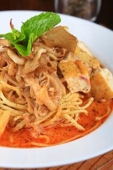 Bord soep met spaghetti, stukjes brood en versierd met greens